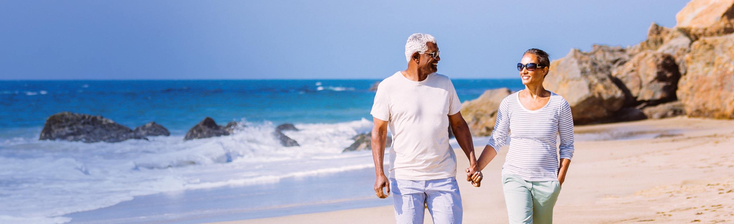 손 잡고 해변에서 걷고 있는 노부부
